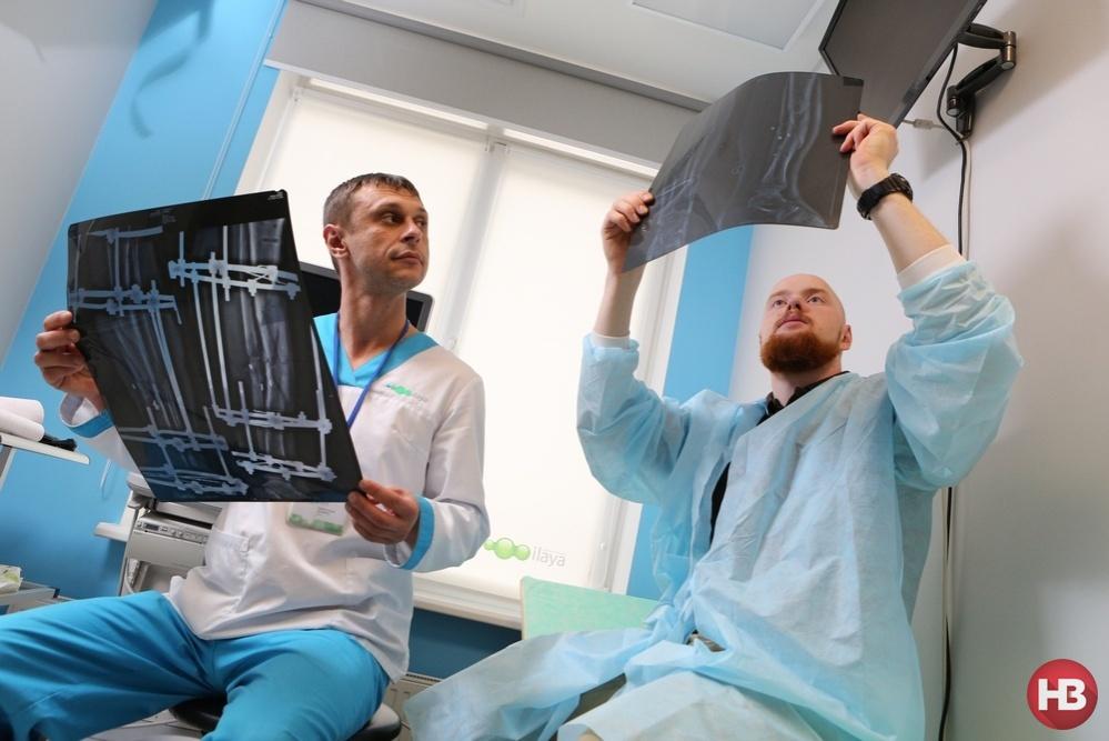 Роман Васильев (на фото слева) и его пациент Олег Толмачев, доброволец батальона Азов, рассматривают послеоперационные снимки. Результатом довольны оба